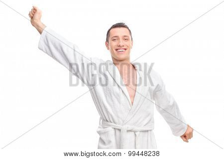 Cheerful young guy in a white bathrobe stretching himself isolated on white background