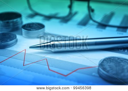 Pen, Gasses And Coin On Financial Chart And Graph