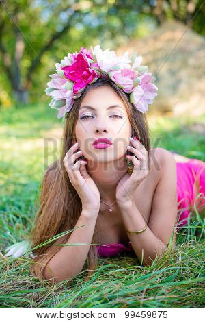 Pretty lady with long hair in wreath on grass