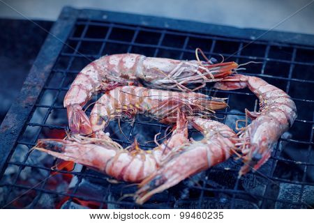 Shrimps on charcoal grill, outdoor picnic, blue toned image