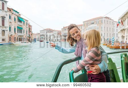 Mother Pointing Out Sights To Daughter While On A Boat Ride