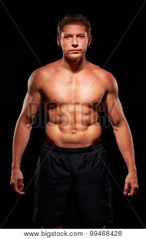 Strong heavy muscular man with naked torso and pursed lips dressed in black shorts and isolated on b
