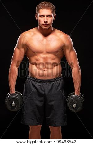 Serious powerful muscular body of young sportsman standing shirtless with black dumbbells