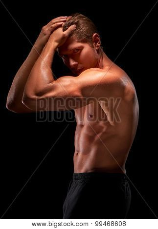 Sexy male shirtless muscular sportsman standing with hands on head demonstrating biceps triceps and