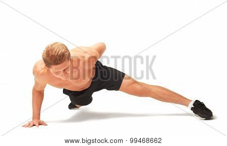 Young muscular handsome shirtless sportsman doing push-ups on one arm isolated on white