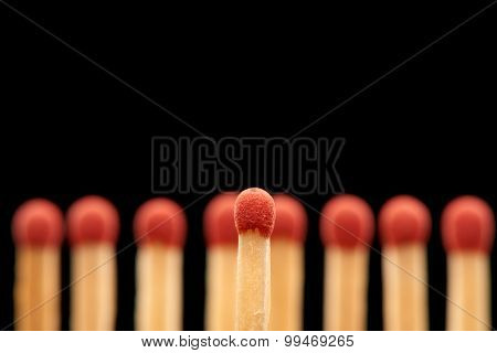 Red match standing in front of red wooden matches