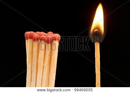 Group of red wooden matches standing with burning match