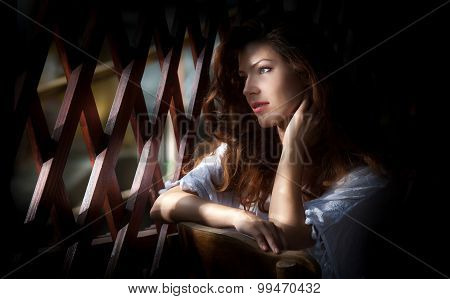 Charming young light brown hair woman looking through wooden grid. Sexy gorgeous young woman