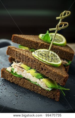 Delicious sandwiches dark bread on skewers with avocado, chicken, dressing,