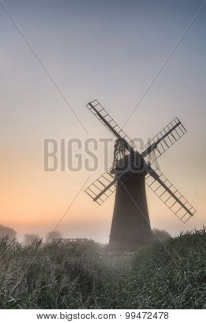 Windmill In Stunning Landscape On Beautiful Summer Dawn