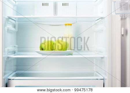 Two green apples on white plate and a glass bottle of yoghurt in open empty refrigerator