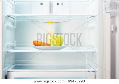Apple and carrot with bottle of yoghurt in refrigerator