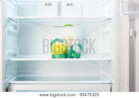 Apple with measuring tape and bottle on shelf of refrigerator