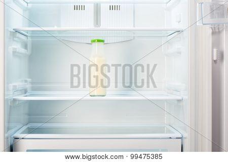 Glass bottle of yoghurt on shelf of open empty refrigerator