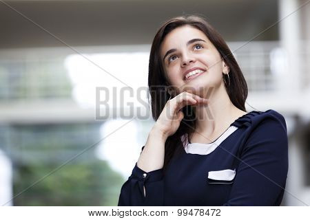 Business woman looking up at modern office building