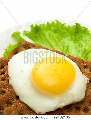 Healthy breakfast background: fried eggs, lettuce, crisp bread