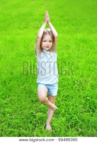 Little Girl Child On The Grass Does Yoga Exercise Outdoors In Summer Day