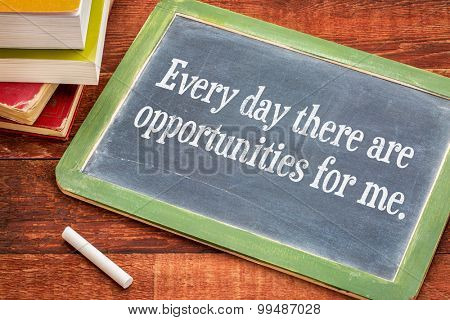 Every day there are opportunities for me - positive affirmation phrase on a slate blackboard with a white chalk and a stack of books against rustic wooden table