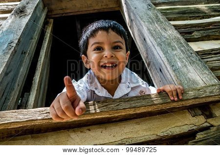 Latino Child Looking Out A Window