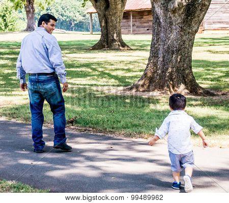 Latino Father And Child Walking Outside