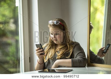 Teenage girl is sitting at a table typing on a smartphone.