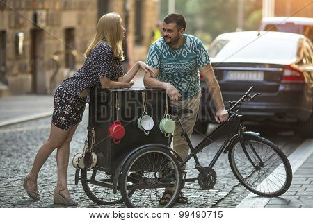 Young beautiful woman flirts with a man near vintage bike on the street.