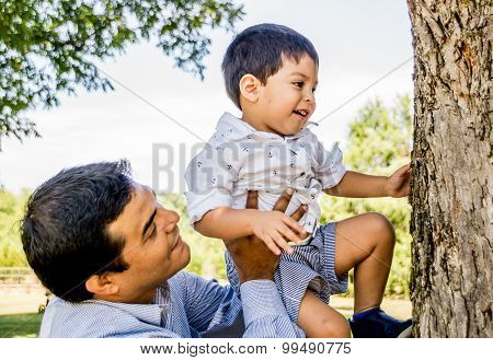Latino Father Holding Son Up To A Tree
