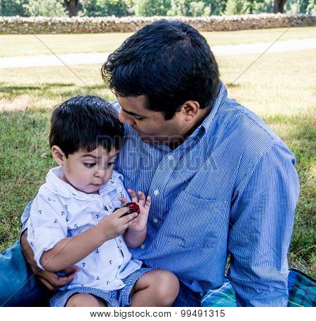Latino Father Holding Son Outside
