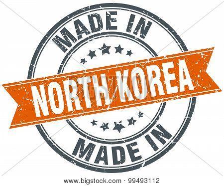 North Korea Orange Grunge Ribbon Stamp On White