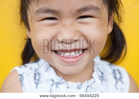 Close Up Face Of Asian Kid Toothy Smiling Facial Face With Happiness Emotion On Yellow Wall Use For