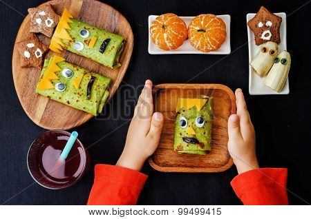 Childrens Hands Holding Plate With Lunch In The Form Of Monsters For Halloween