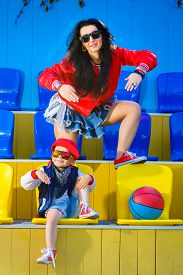 stock photo of rap-girl  - Rapper attitude rap singer hip Hop Dancer performing. Stylish woman and little boy posing at basketball court.
