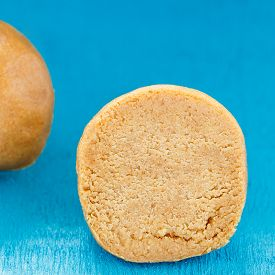 stock photo of laddu  - The indian sweet ball laddu on blue wooden table - JPG