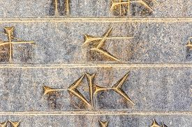 image of zoroastrianism  - Part of ancient cuneiform closeup detail on the stairway facade of the Apadana at the Persepolis - JPG