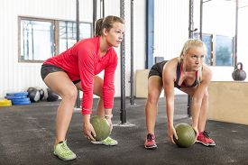 stock photo of slam  - Young women lifts slam balls at the fitness gym center - JPG