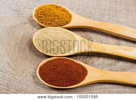 Spice Powder On A Wooden Background. Closeup On Paprika, Curry And Ginger.
