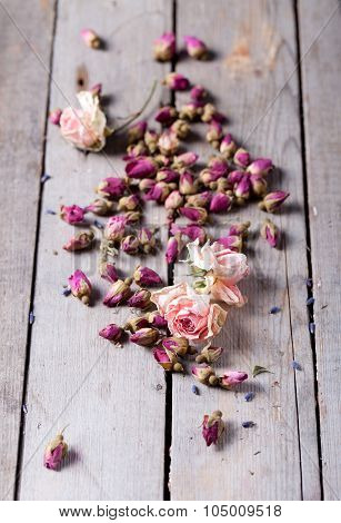Dried rose buds scattered on a wooden table