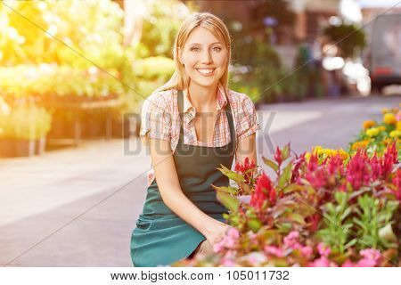 Happy young woman as gardener in front of a flower shop