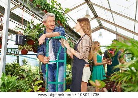 Gardener trainee in nursery shop talking with employee