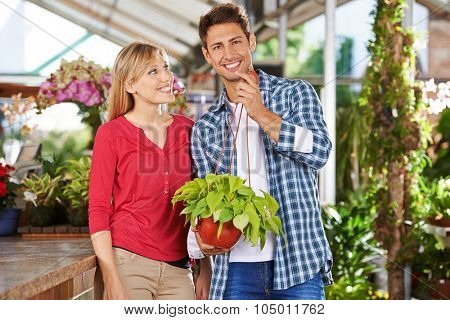 Happy couple with a philodendron plant in a garden center