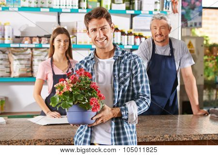 Gardener and florist as staff in nursery shop at the checkout counter