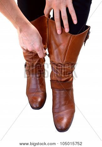Woman Holds Her Brown Leather Boots While Zipping Them Up