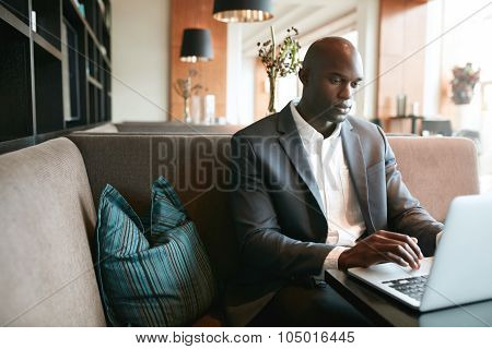 Young Man Sitting At Cafe Working On Laptop