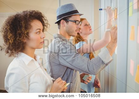 Business people writing on adhesive notes on glass wall during meeting in office