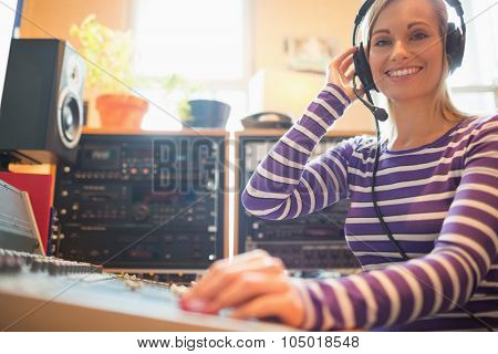 Portrait of young radio host using sound mixer in studio