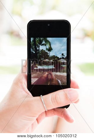 Hand of young caucasian woman who is holding cellphone and taking picture of her legs near with pool
