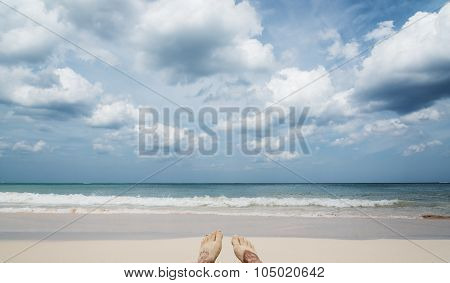 Feet on the beach with wide sea horizon, focus on waves
