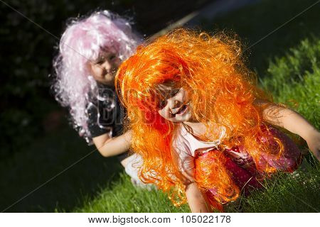 Two Little Girls Sister The Same Age In Colored Wigs Playing On The Lawn In The Garden.