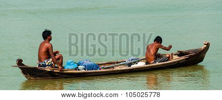 Two Asian men rowing wooden boat on a river