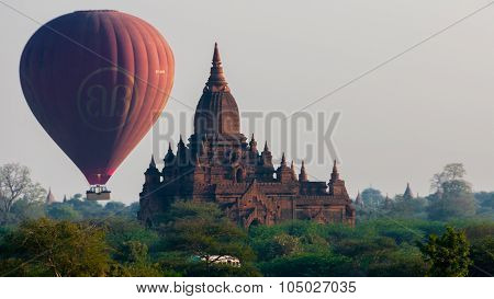 Hot air balloon behind temple in Bagan